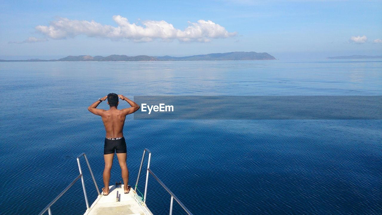 Full length rear view of shirtless man sailing on boat in sea against sky