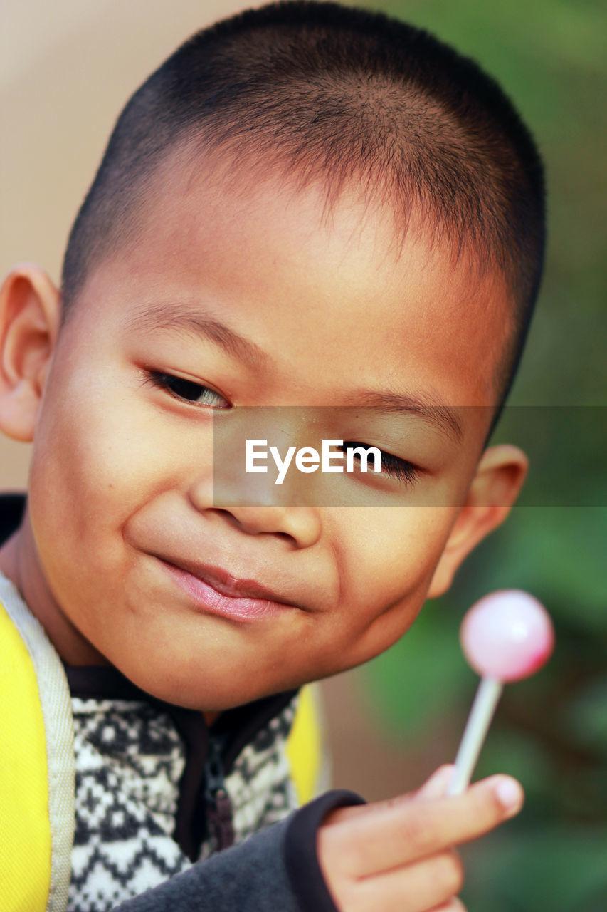 Close-up of cute boy holding lollipop