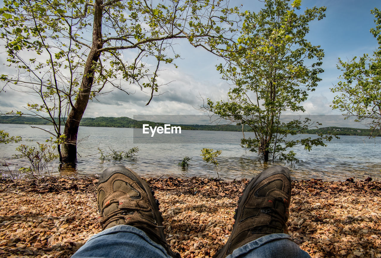 water, low section, tree, shoe, personal perspective, human leg, body part, real people, plant, human body part, one person, sky, nature, lake, beauty in nature, day, scenics - nature, lifestyles, jeans, outdoors, human foot, human limb