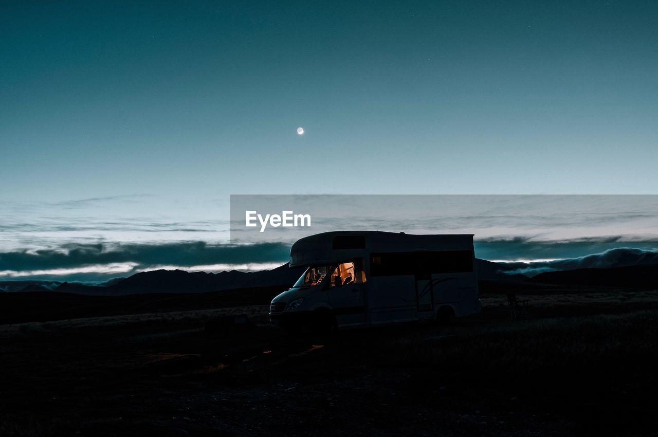 Vehicle On Field Against Sky At Dusk