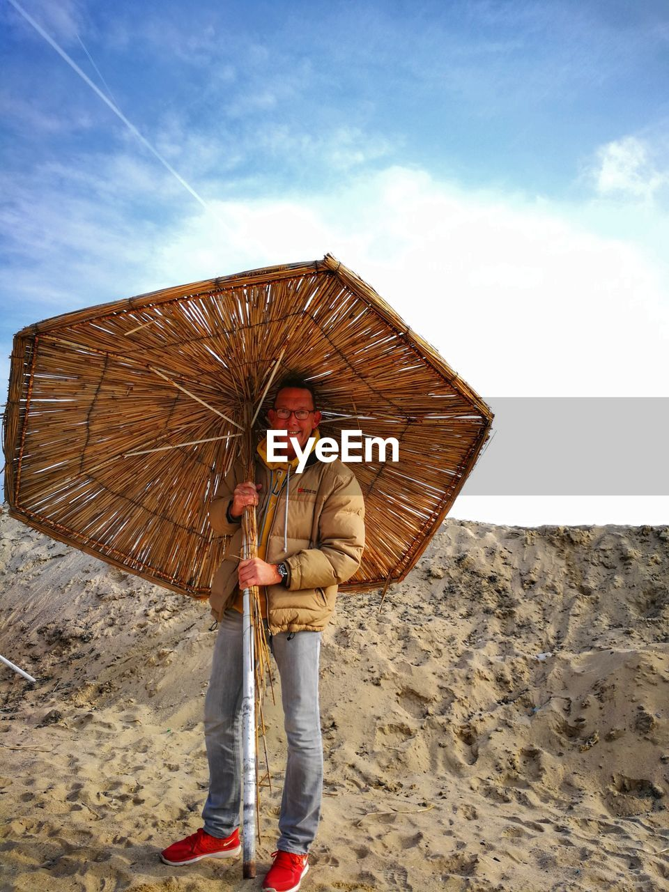 Portrait of smiling man with thatched umbrella standing on beach