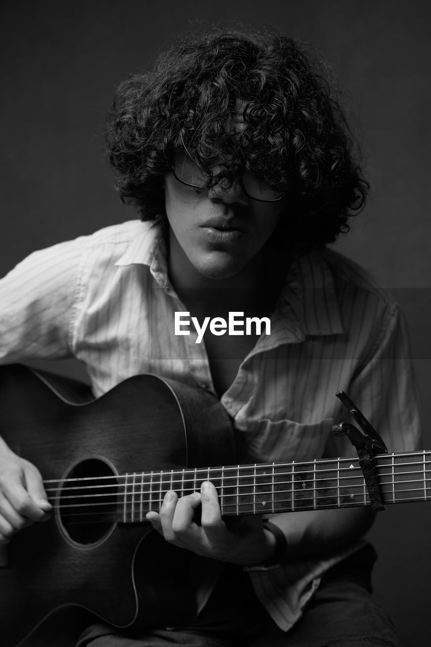 music, string instrument, musical instrument, guitar, one person, playing, arts culture and entertainment, real people, front view, musical equipment, holding, artist, sitting, musician, plucking an instrument, men, lifestyles, leisure activity, skill, acoustic guitar, teenager, hairstyle