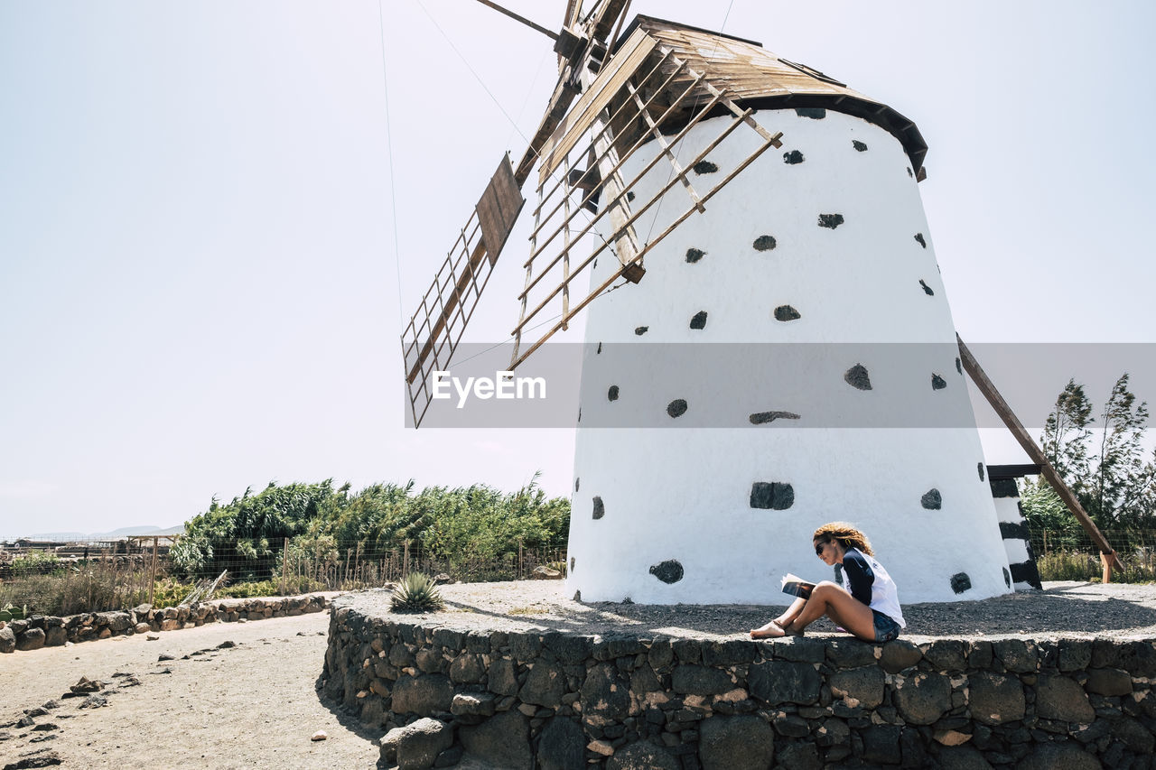 Side View Of Woman Sitting Against Traditional Windmill