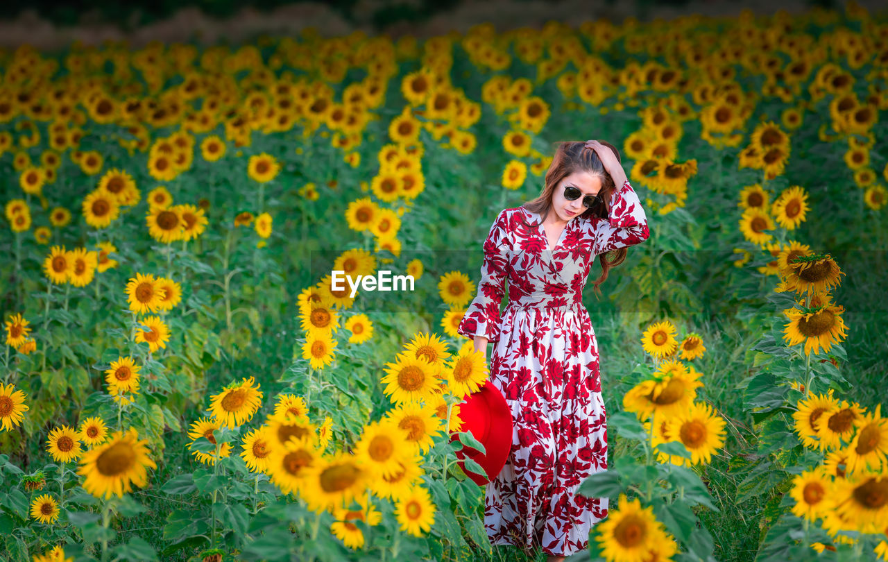 flower, plant, one person, yellow, flowering plant, women, standing, front view, fashion, growth, young adult, pattern, green color, dress, clothing, nature, freshness, lifestyles, floral pattern, sunflower, outdoors, flower head, hairstyle