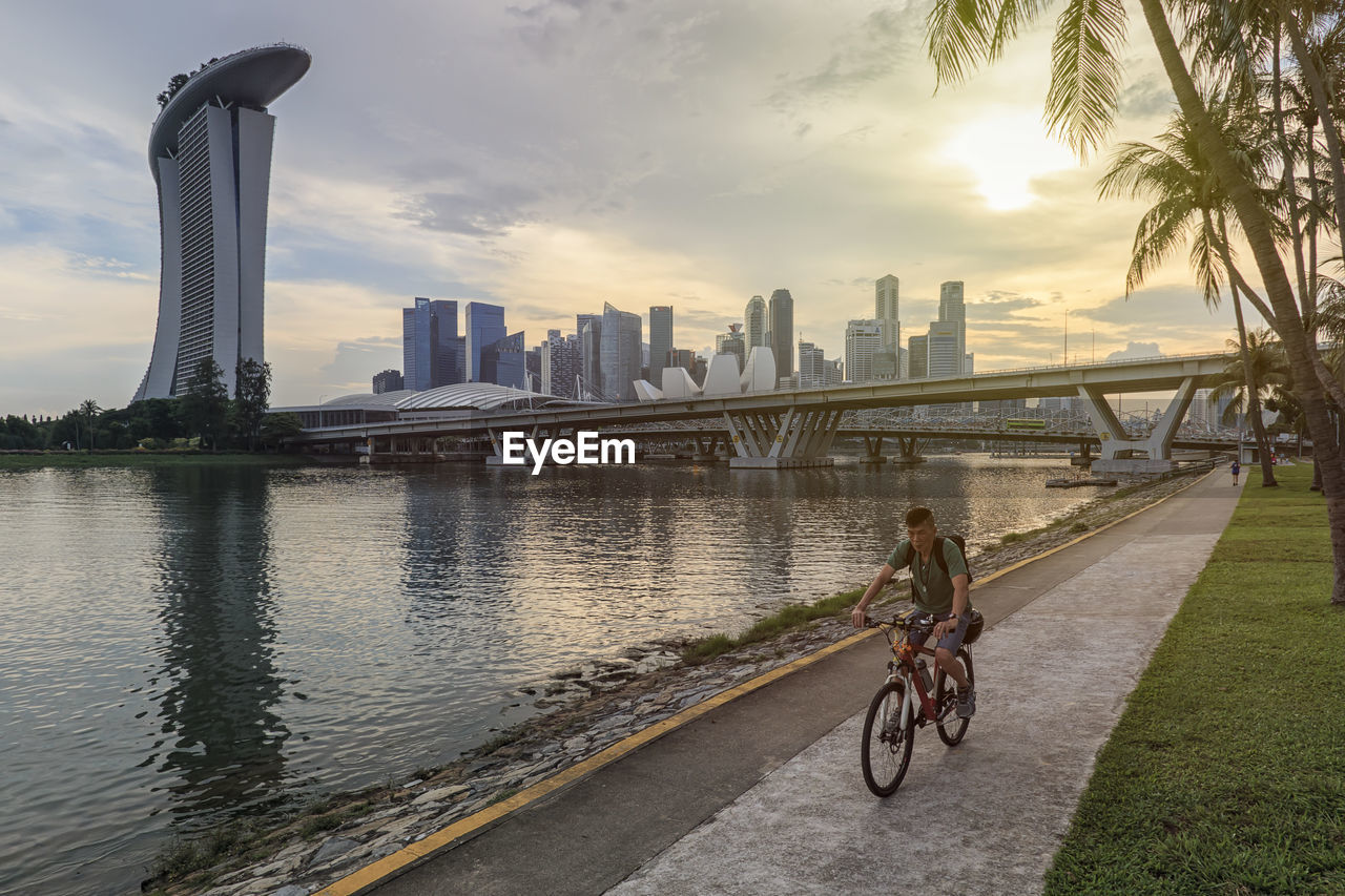water, transportation, bicycle, built structure, sky, architecture, building exterior, city, lifestyles, river, nature, bridge, riding, ride, activity, bridge - man made structure, cycling, land vehicle, sport, office building exterior, outdoors, cityscape, skyscraper