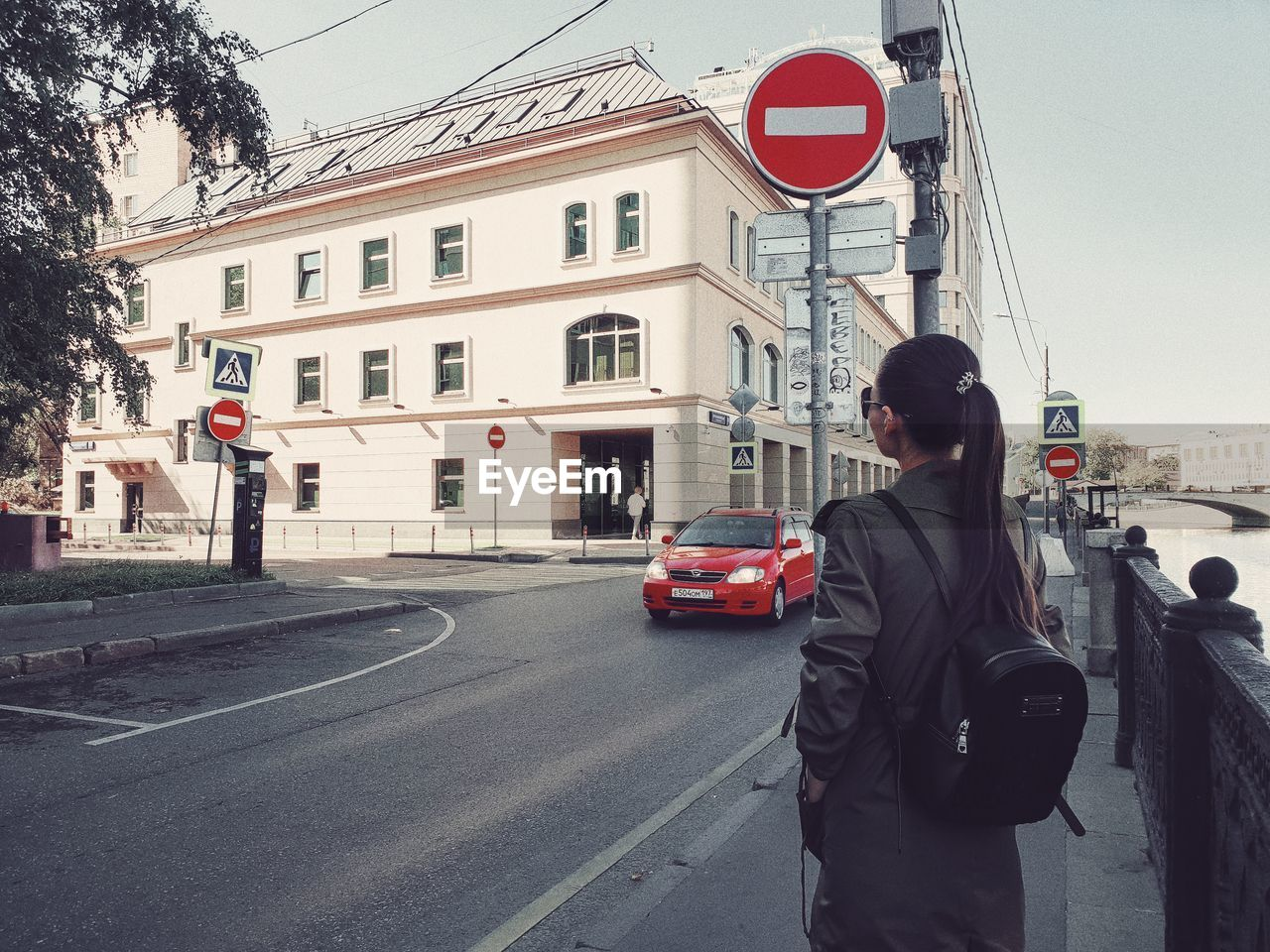 city, transportation, architecture, one person, motor vehicle, sign, car, building exterior, built structure, mode of transportation, real people, road, street, land vehicle, standing, road sign, three quarter length, city life, day, outdoors