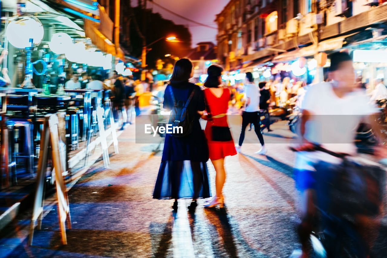 Rear view of women standing in illuminated street