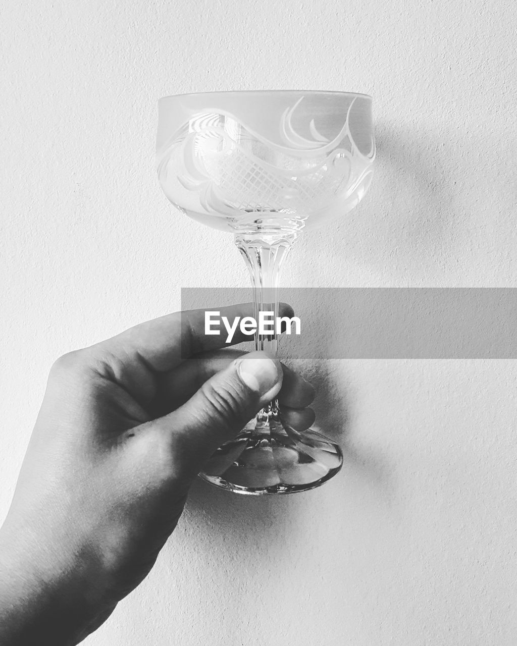 Cropped hand of man holding wineglass against wall
