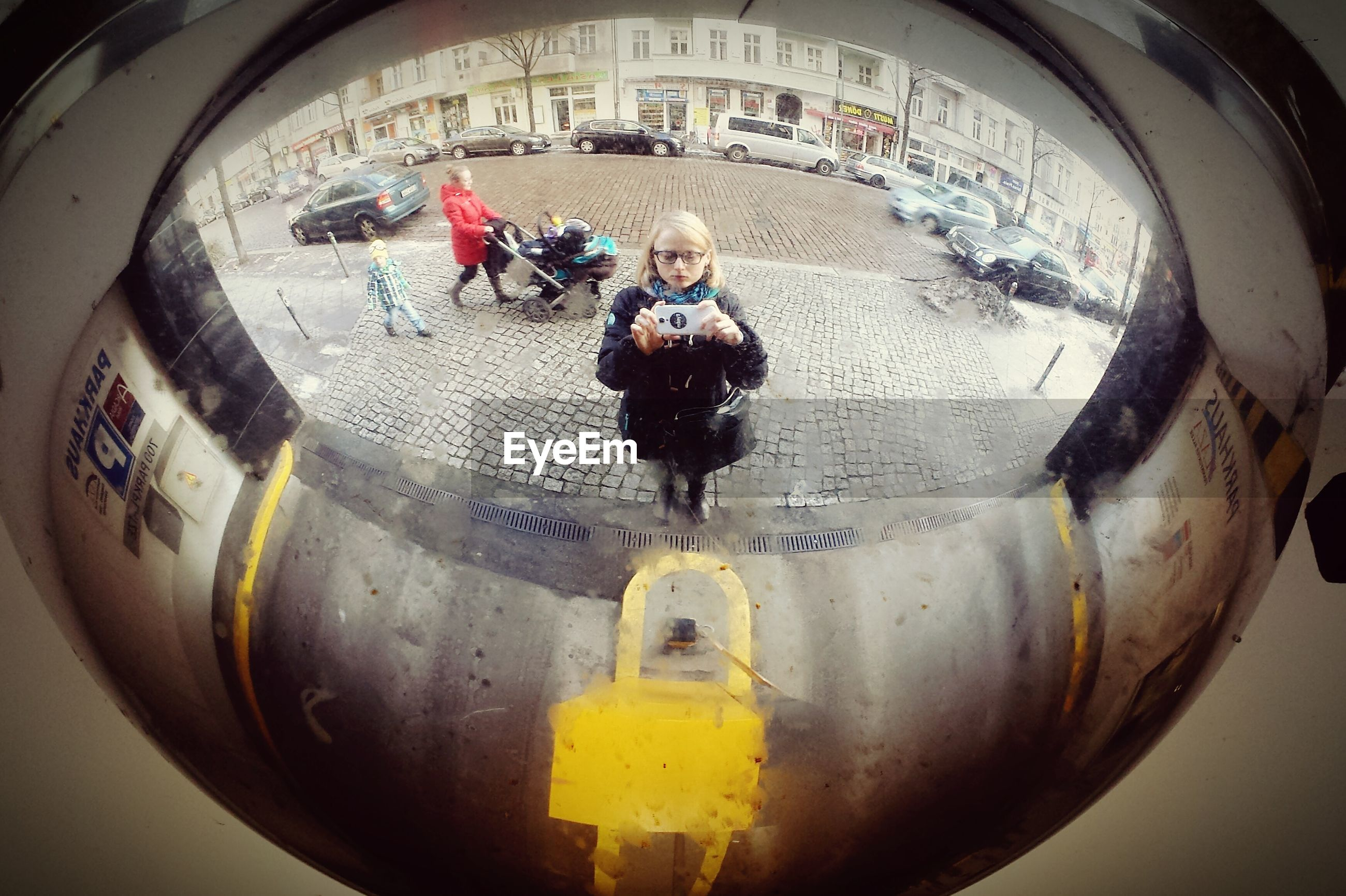 Woman taking selfie on mirror against buildings and cars in city