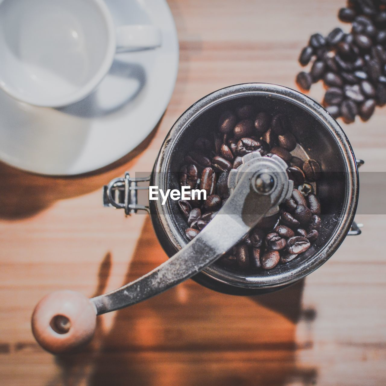 close-up, no people, table, high angle view, indoors, metal, still life, equipment, food and drink, wood - material, directly above, cup, drink, focus on foreground, handle, machine part, coffee - drink, black color, day, selective focus, silver colored