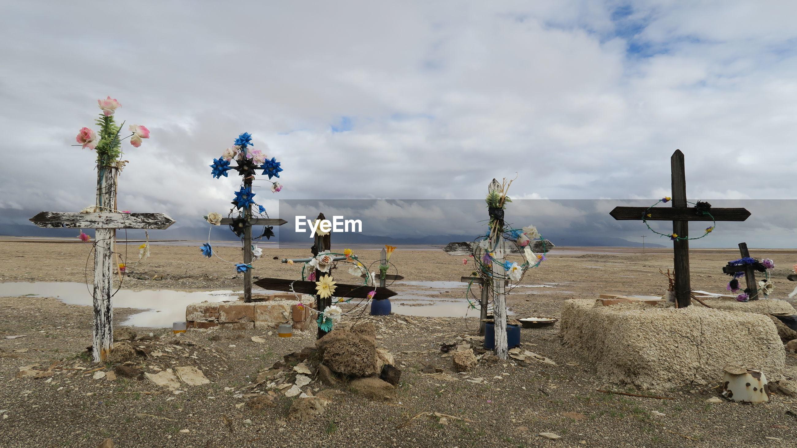 Religious cross on landscape against sky