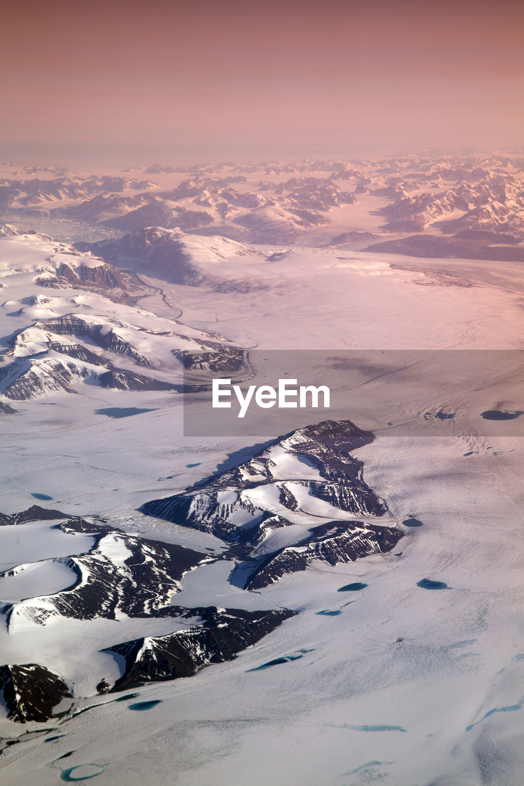Aerial view of snow covered land and mountains against sky