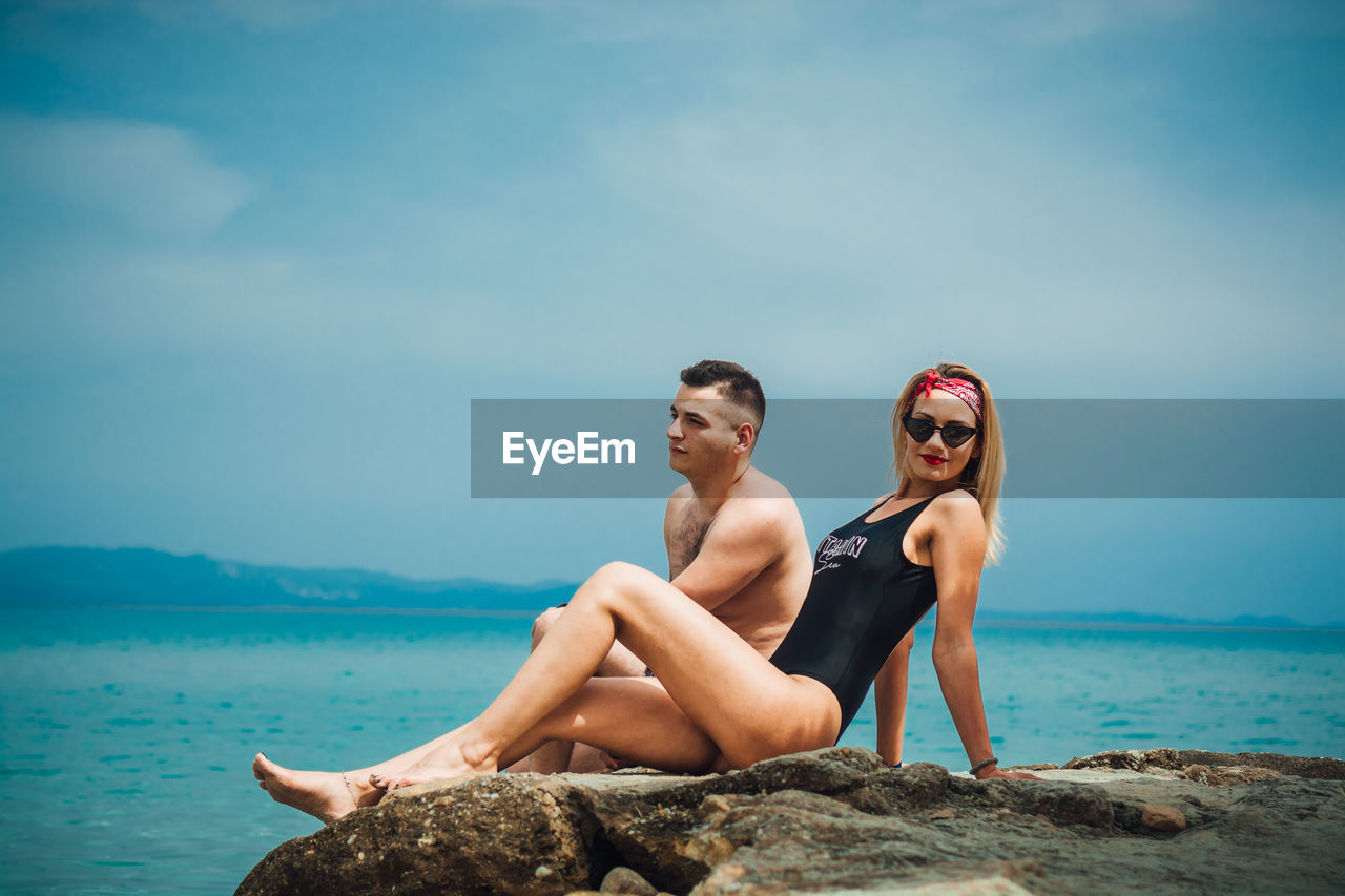 water, sky, two people, leisure activity, sea, shirtless, lifestyles, young adult, togetherness, real people, nature, young women, young men, couple - relationship, men, sitting, smiling, heterosexual couple, fashion