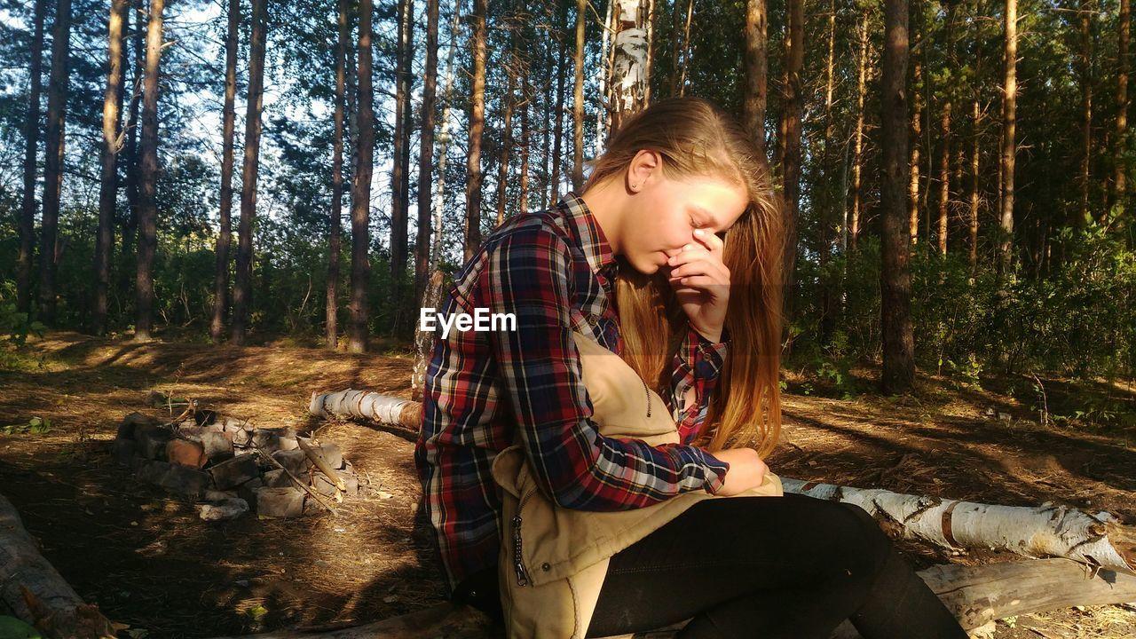 Portrait Of Teenage Girl Sitting Outdoors