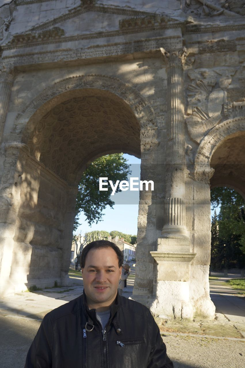 Portrait of mid adult man standing by triumphal arch