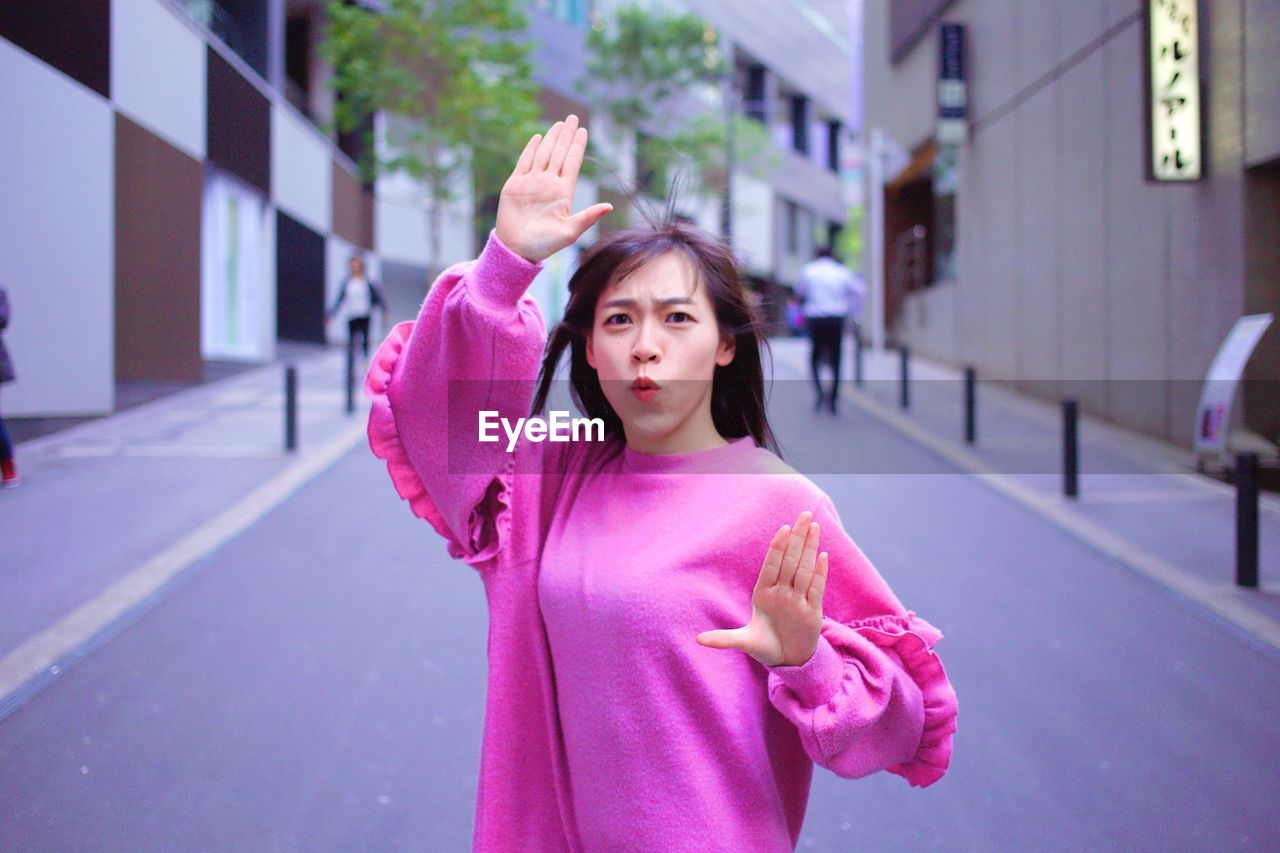 one person, real people, lifestyles, standing, pink color, architecture, women, city, building exterior, leisure activity, built structure, focus on foreground, young adult, females, casual clothing, waist up, front view, human arm, gesturing, arms raised, outdoors, hairstyle, purple