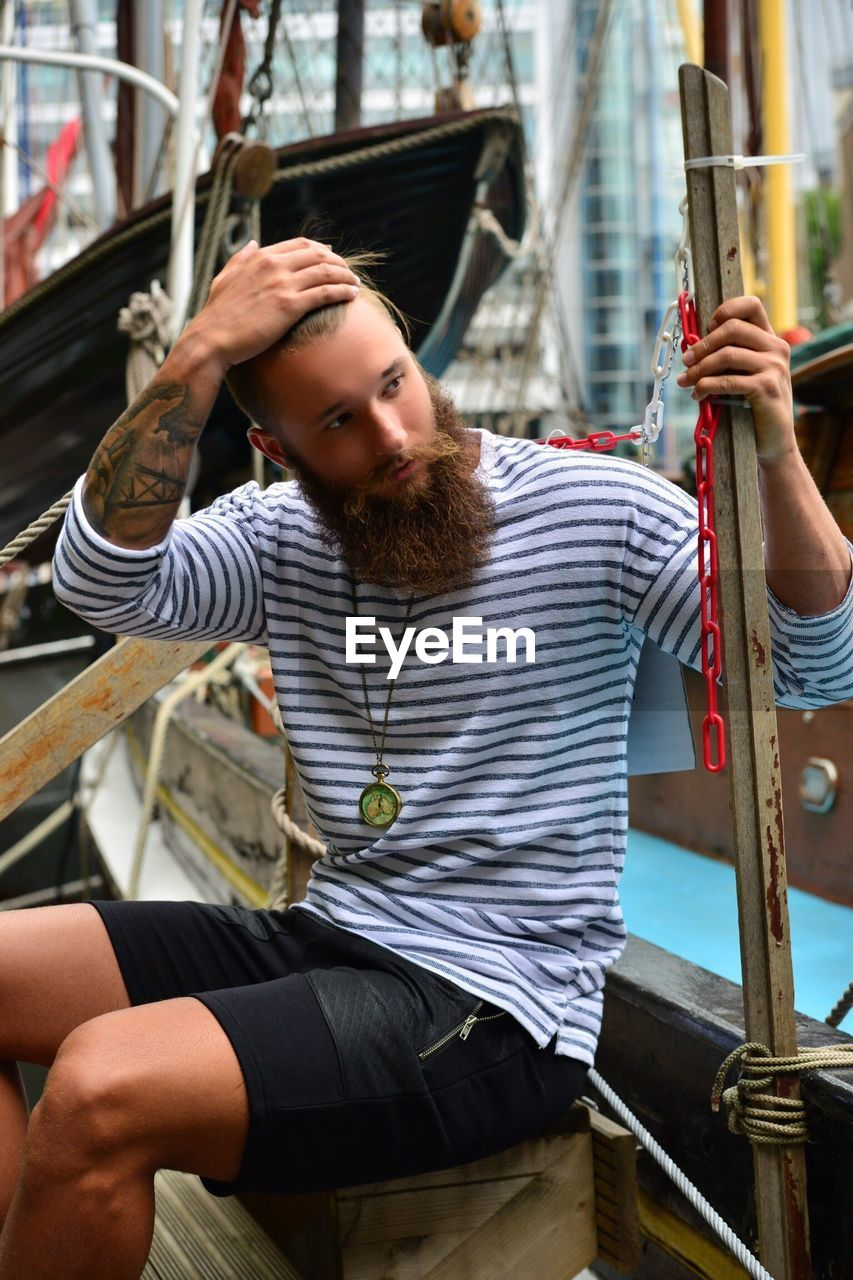 Hipster Looking Away While Sitting In Boat