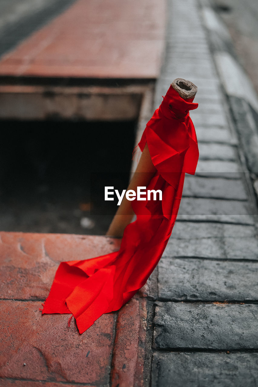 red, focus on foreground, day, no people, outdoors, architecture, clothing, wood - material, built structure, full length, footpath, nature, selective focus, staircase, scarf, textile, fashion, transportation