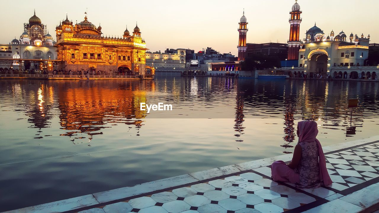 Woman praying by golden temple against sky at dusk