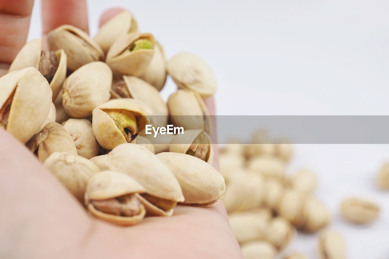 food and drink, food, nut, freshness, wellbeing, nut - food, healthy eating, close-up, large group of objects, human hand, one person, selective focus, hand, human body part, still life, indoors, focus on foreground, pistachio, nutshell, cashew, snack, finger