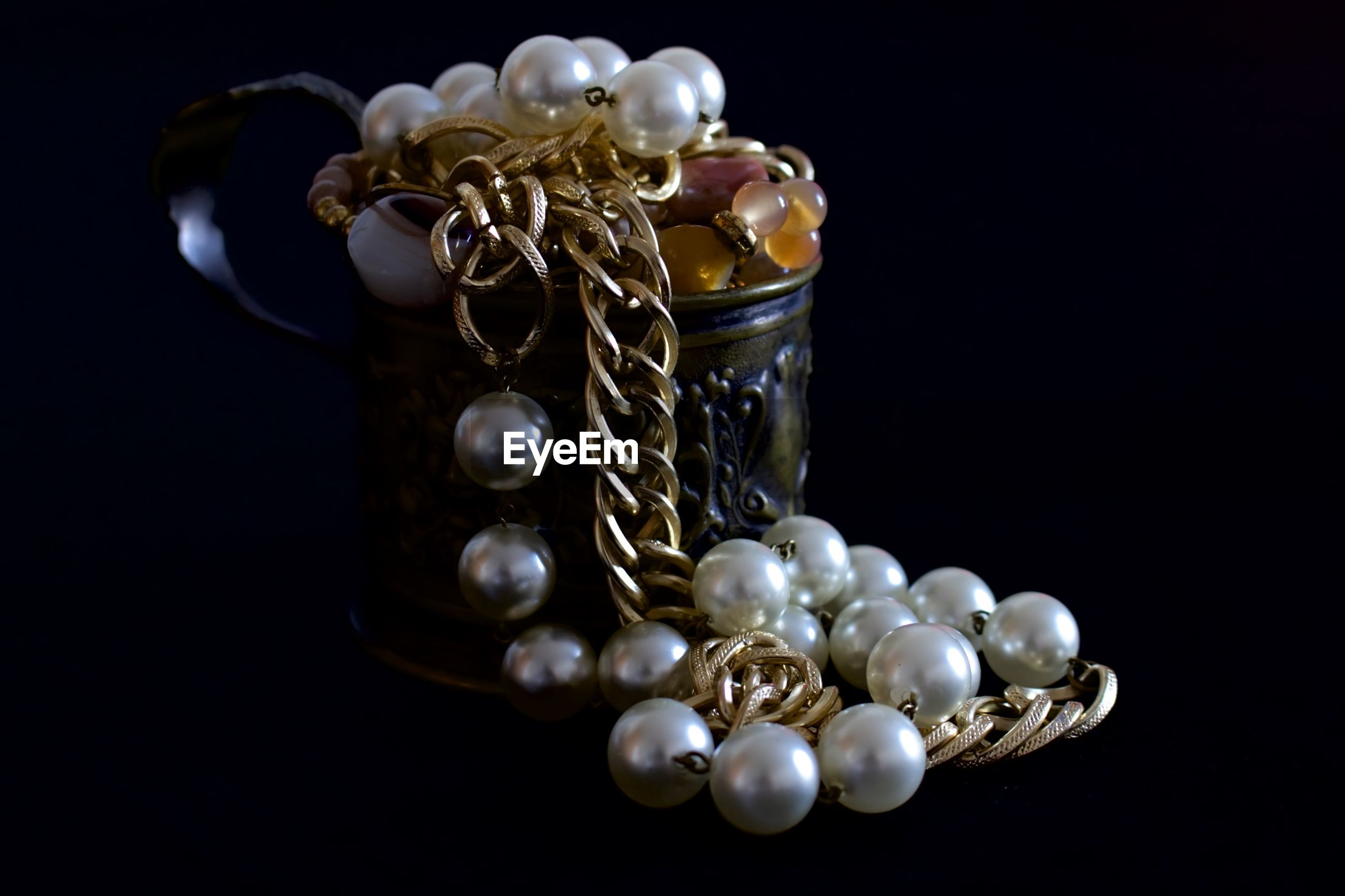 Close-up of pearl necklace in container against black background