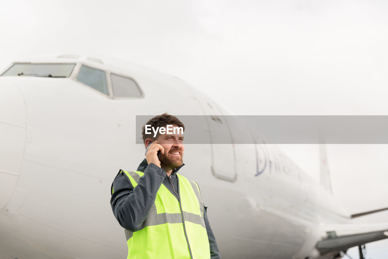 MAN USING MOBILE PHONE WHILE STANDING ON AIRPLANE
