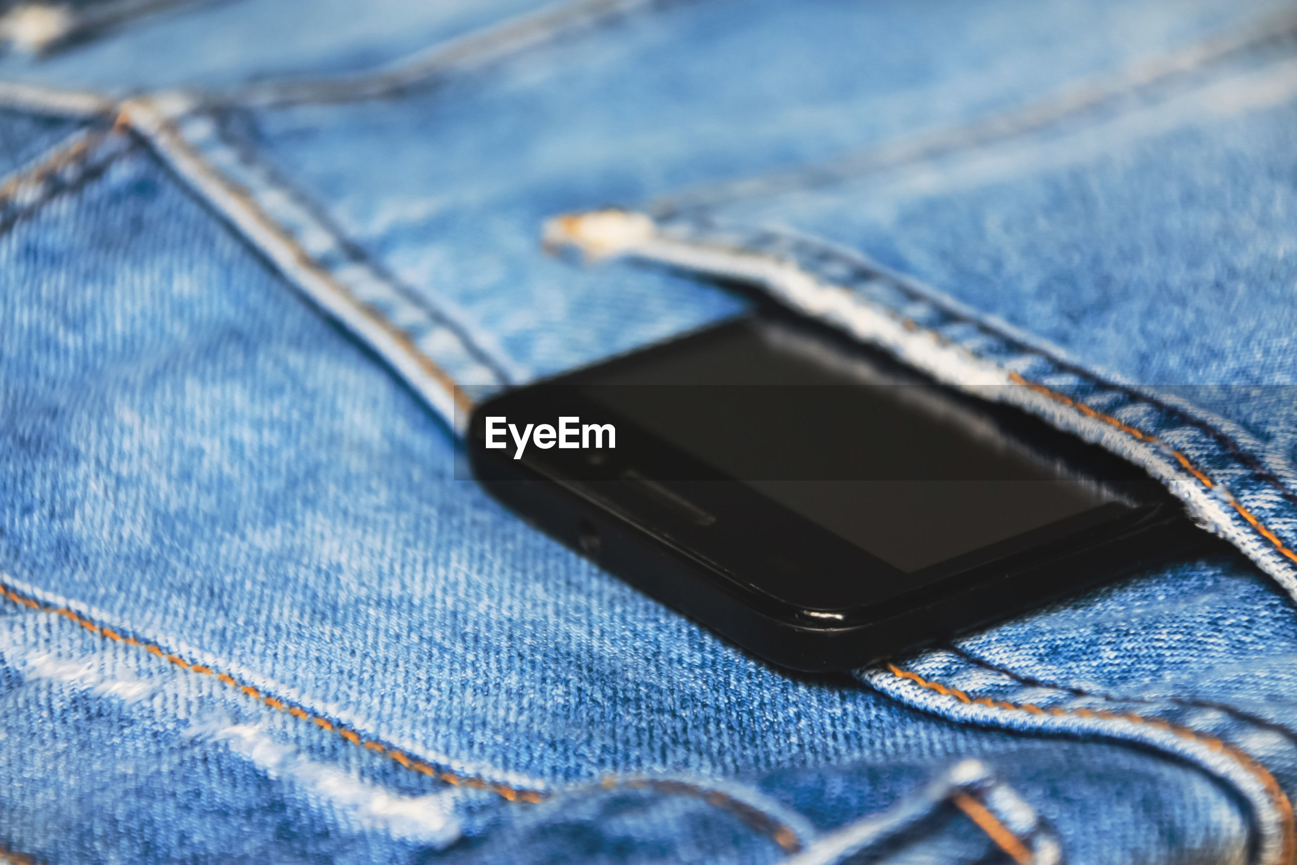 Close-up of phone in jeans pocket