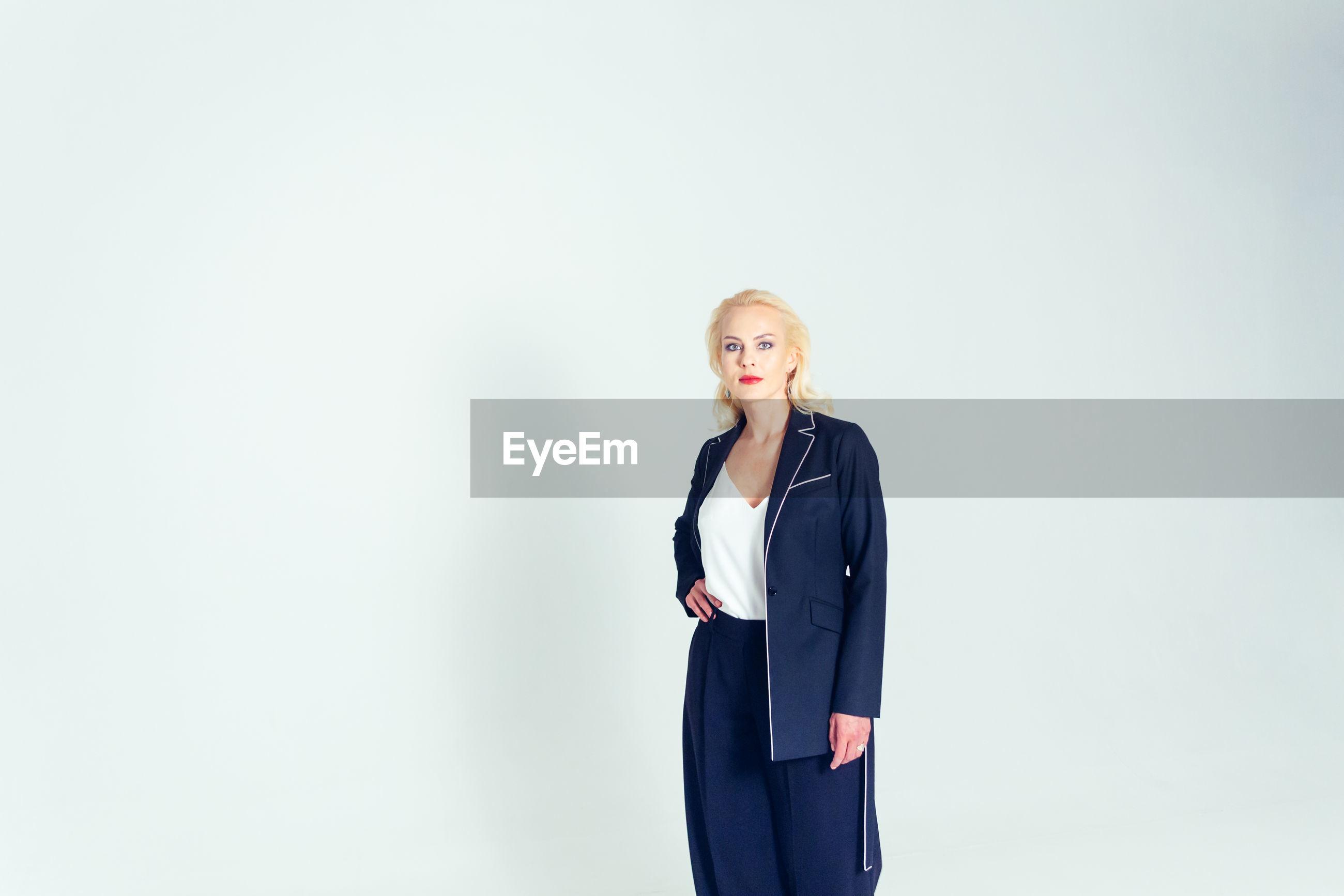 Portrait of confident businesswoman standing against white background