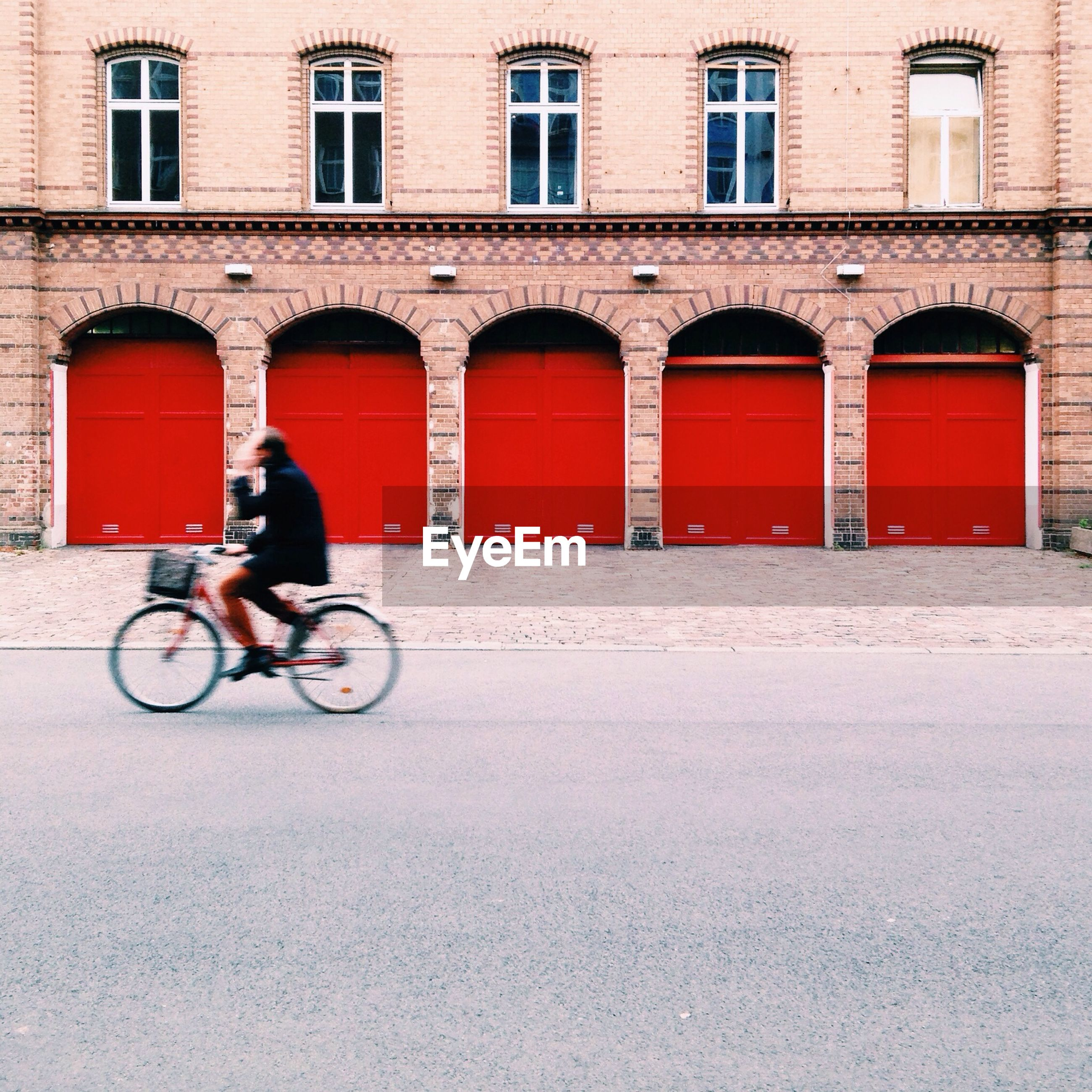 Blurred motion of man riding bicycle on street against building