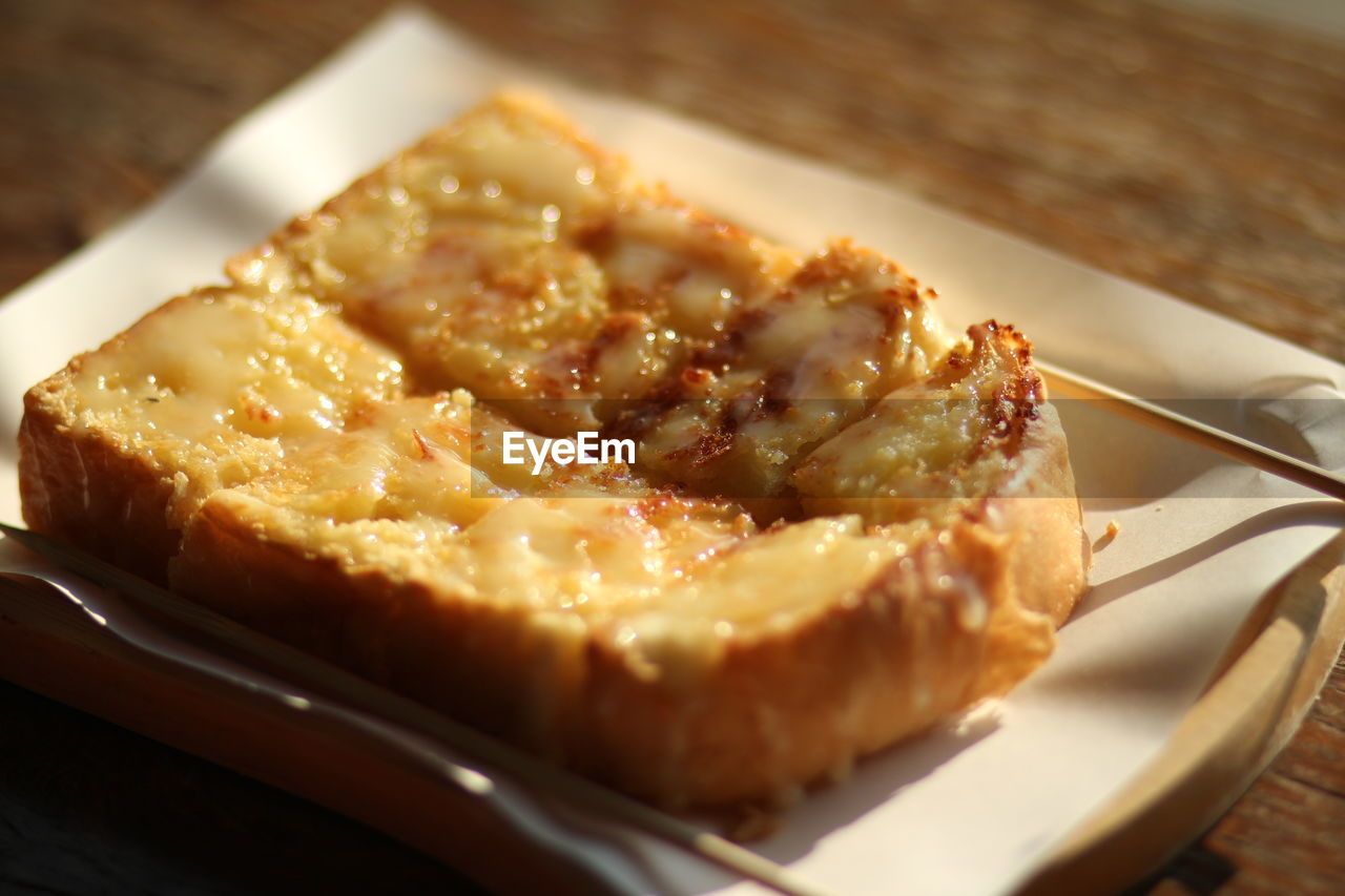Close-Up Of Bread Served In Plate On Wooden Table