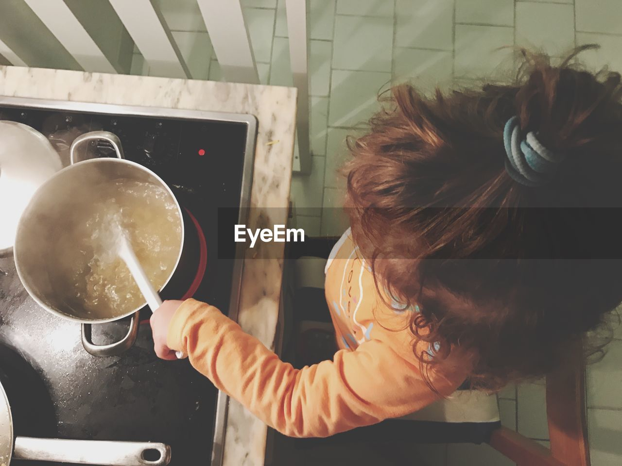 High Angle View Of Girl Preparing Food At Kitchen