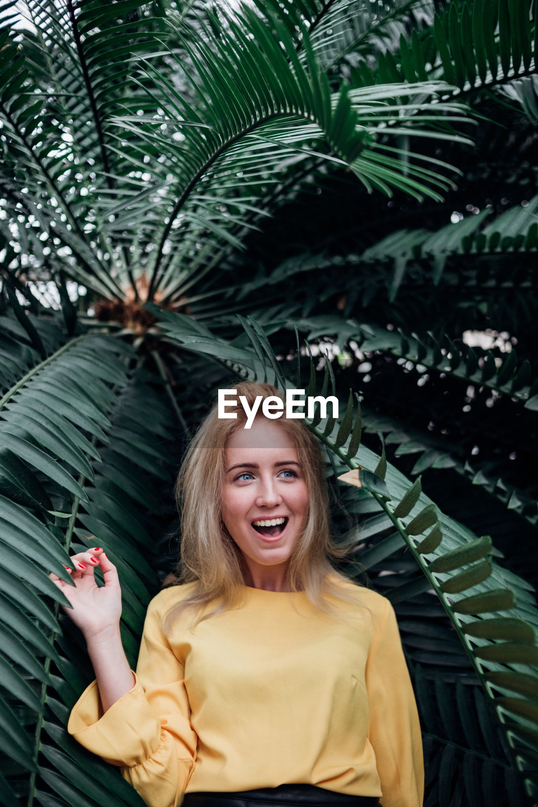 Surprised woman standing against palm tree