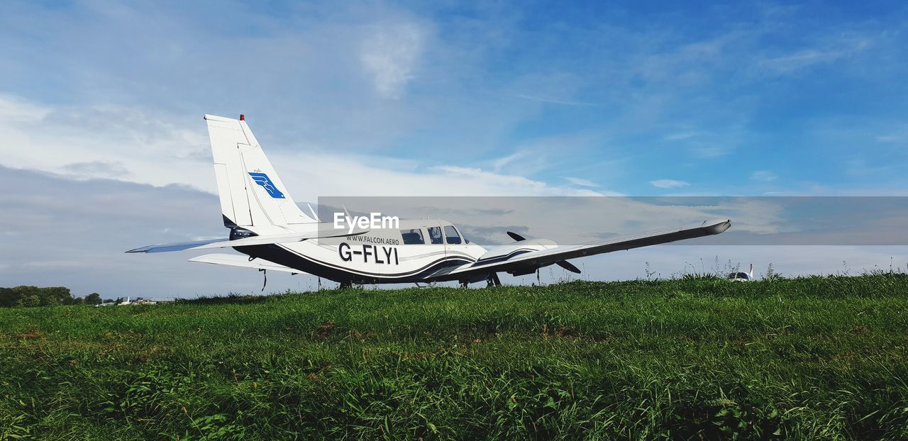air vehicle, airplane, sky, mode of transportation, cloud - sky, grass, transportation, nature, plane, day, plant, no people, field, land, outdoors, fighter plane, military, aerospace industry, growth, on the move