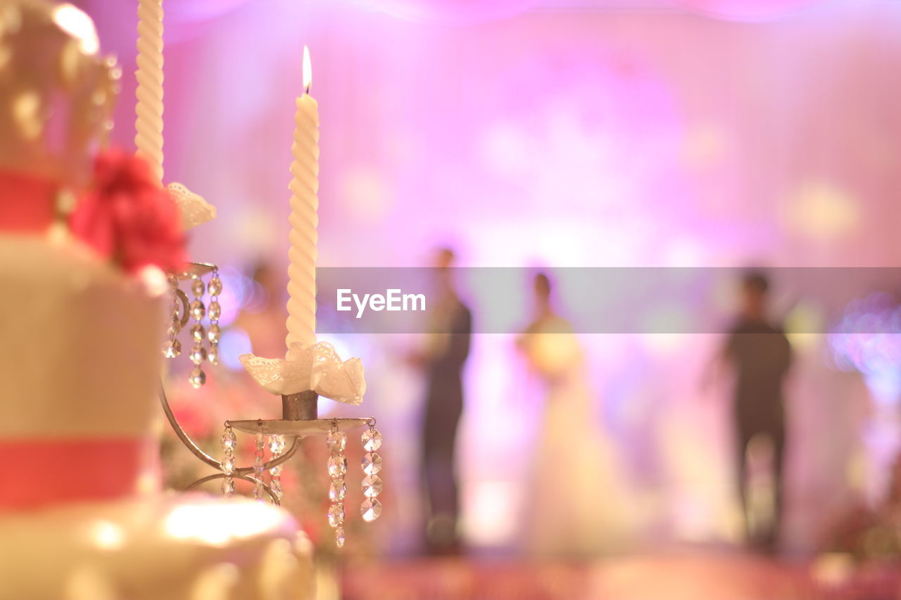 Close-up of lit candles at wedding party