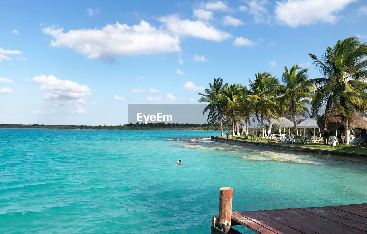 water, sky, sea, tropical climate, palm tree, beauty in nature, tree, scenics - nature, land, nature, cloud - sky, beach, tranquil scene, tranquility, blue, horizon, plant, idyllic, outdoors, horizon over water, no people, turquoise colored, swimming pool