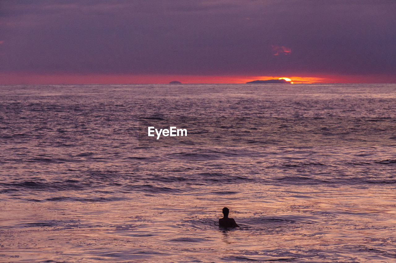 Silhouette man swimming in sea during sunset