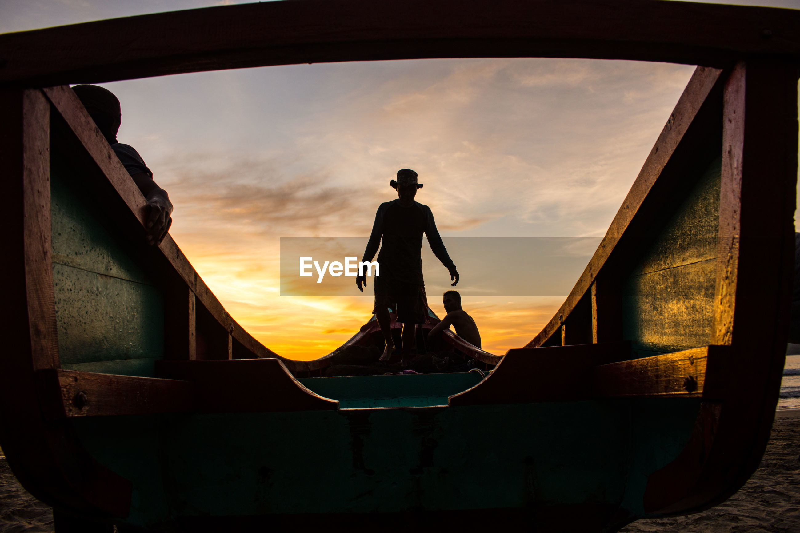 Silhouette of men standing on boat against sky during sunset