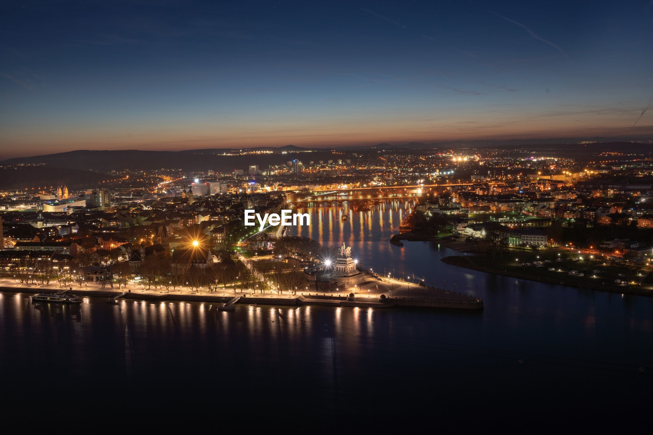 HIGH ANGLE VIEW OF ILLUMINATED CITY BY RIVER AGAINST SKY