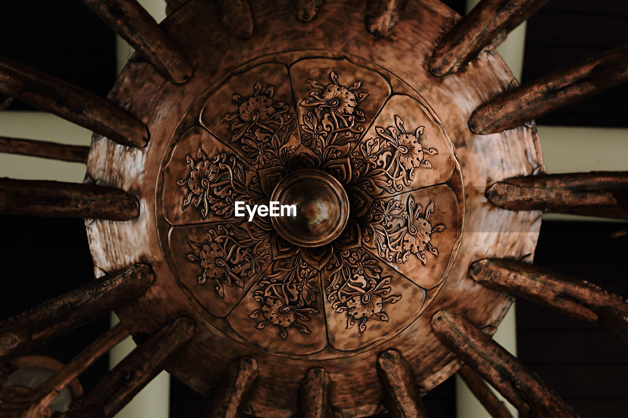 indoors, pattern, creativity, close-up, no people, design, architecture, art and craft, wood - material, low angle view, craft, built structure, focus on foreground, ceiling, building, lighting equipment, ornate, illuminated, metal, shape, directly below, floral pattern