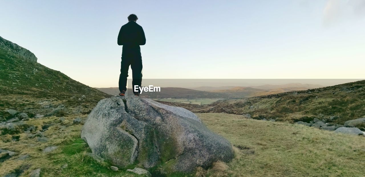 Rear View Of Man On Boulder Against Sky