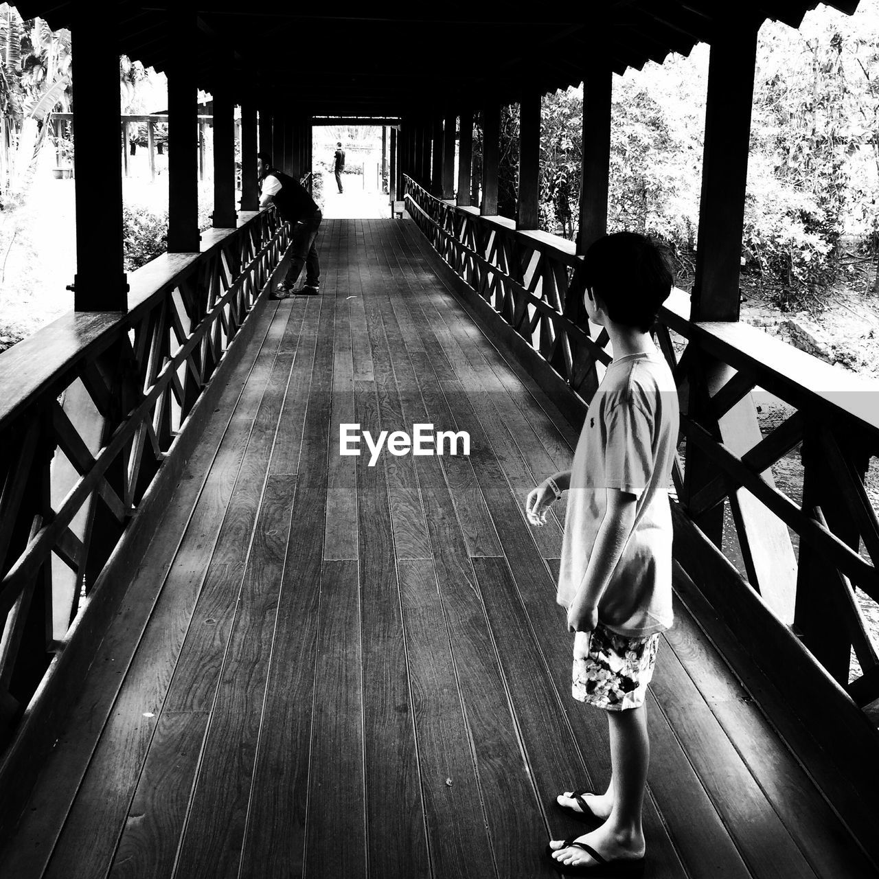 real people, rear view, full length, railing, childhood, one person, the way forward, wood - material, walking, leisure activity, boys, day, tree, built structure, standing, lifestyles, indoors, architecture, wood paneling, people