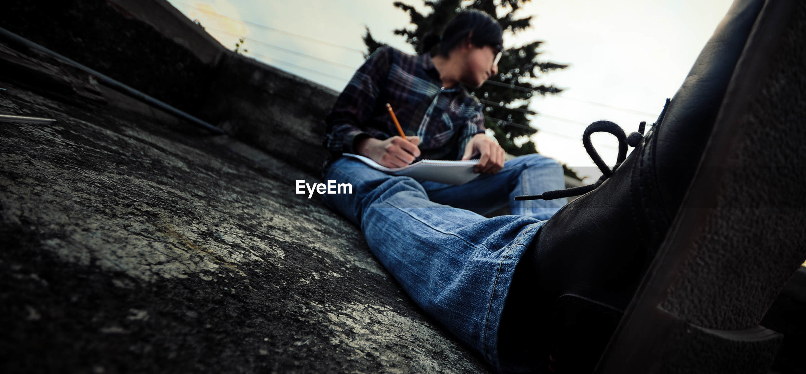 Surface level image of young man looking away while writing on paper at building terrace