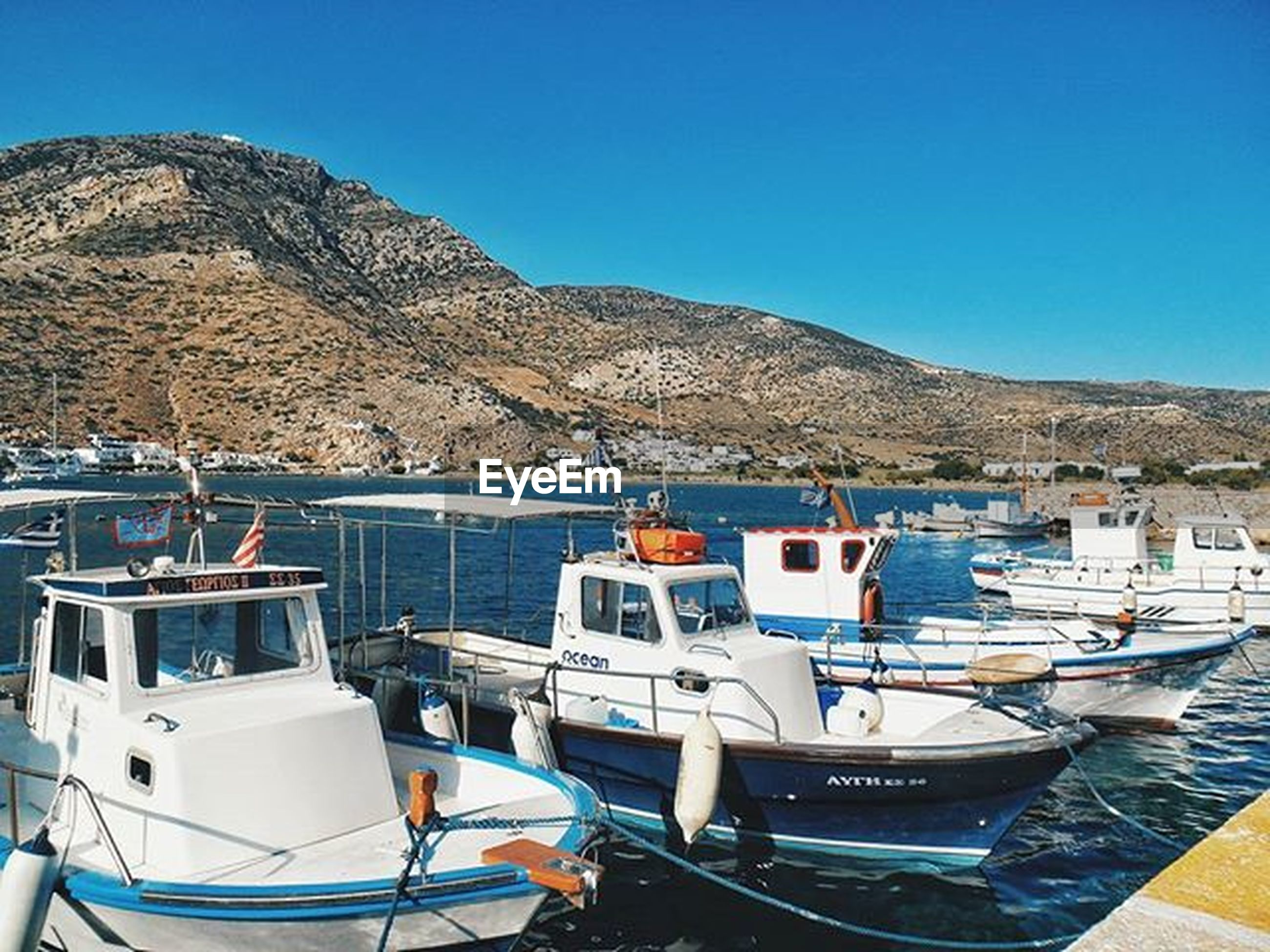 nautical vessel, boat, moored, water, transportation, mountain, mode of transport, sea, clear sky, blue, sky, tranquil scene, nature, tranquility, day, scenics, mountain range, beach, building exterior, travel