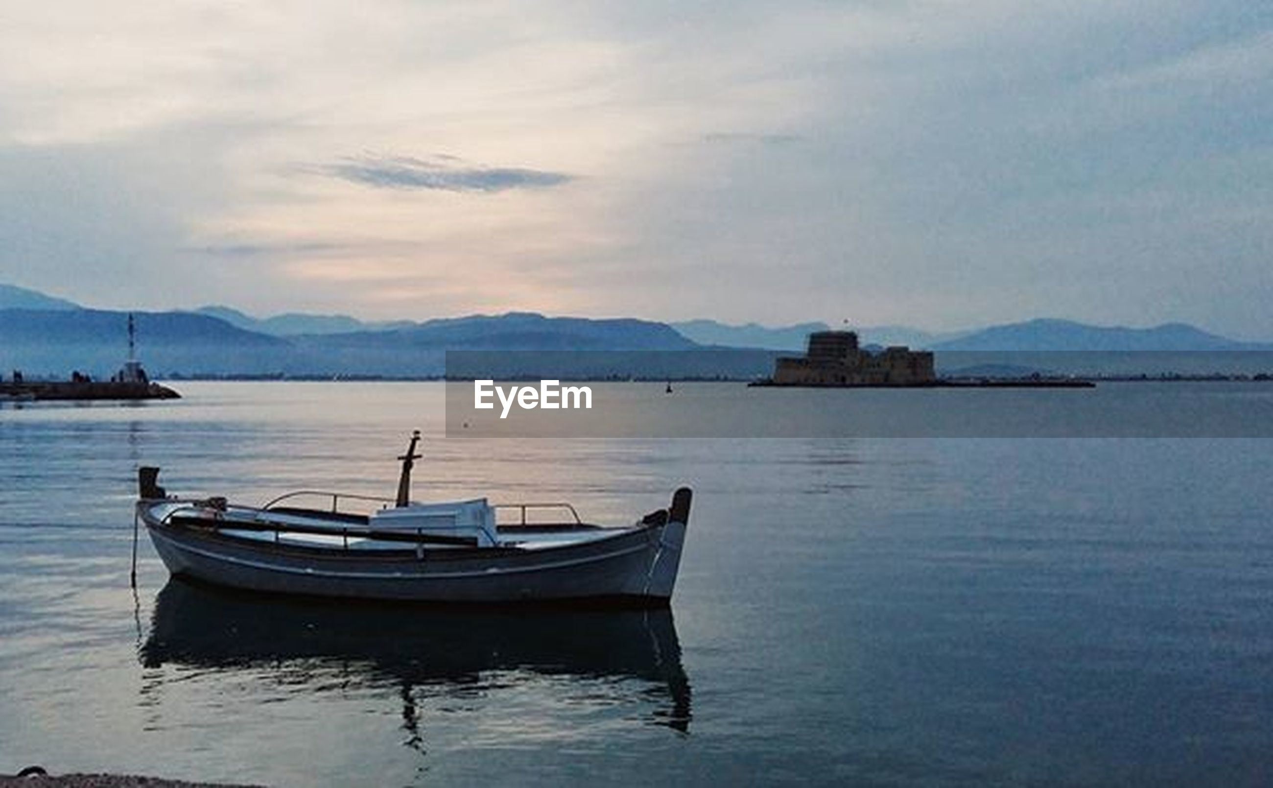 water, nautical vessel, mountain, boat, transportation, sky, moored, mountain range, tranquil scene, mode of transport, waterfront, tranquility, lake, scenics, beauty in nature, cloud - sky, nature, cloud, sea, rippled