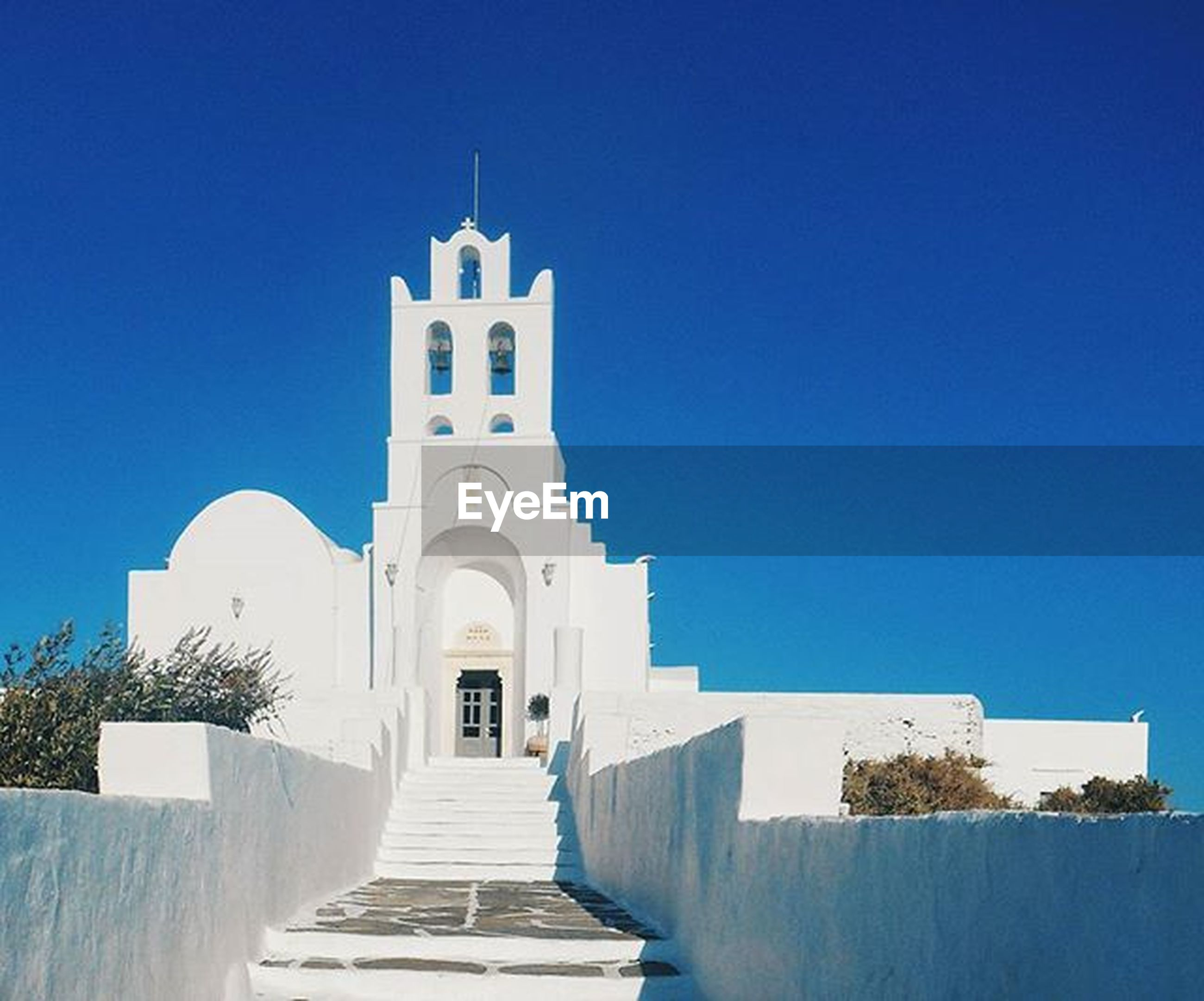 clear sky, architecture, built structure, building exterior, blue, church, place of worship, religion, spirituality, copy space, cross, low angle view, sunlight, day, tower, steps, white color, outdoors