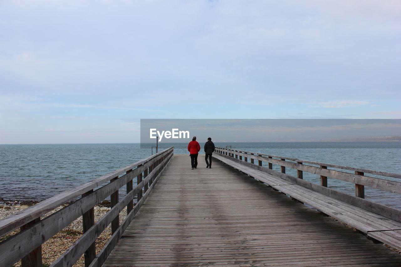 People walking on pier over sea against sky