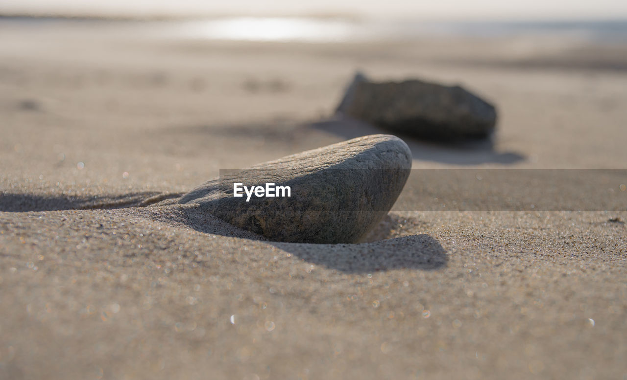 beach, sand, land, nature, selective focus, day, no people, sea, close-up, tranquility, sunlight, outdoors, water, solid, shadow, rock, textured, beauty in nature, surface level