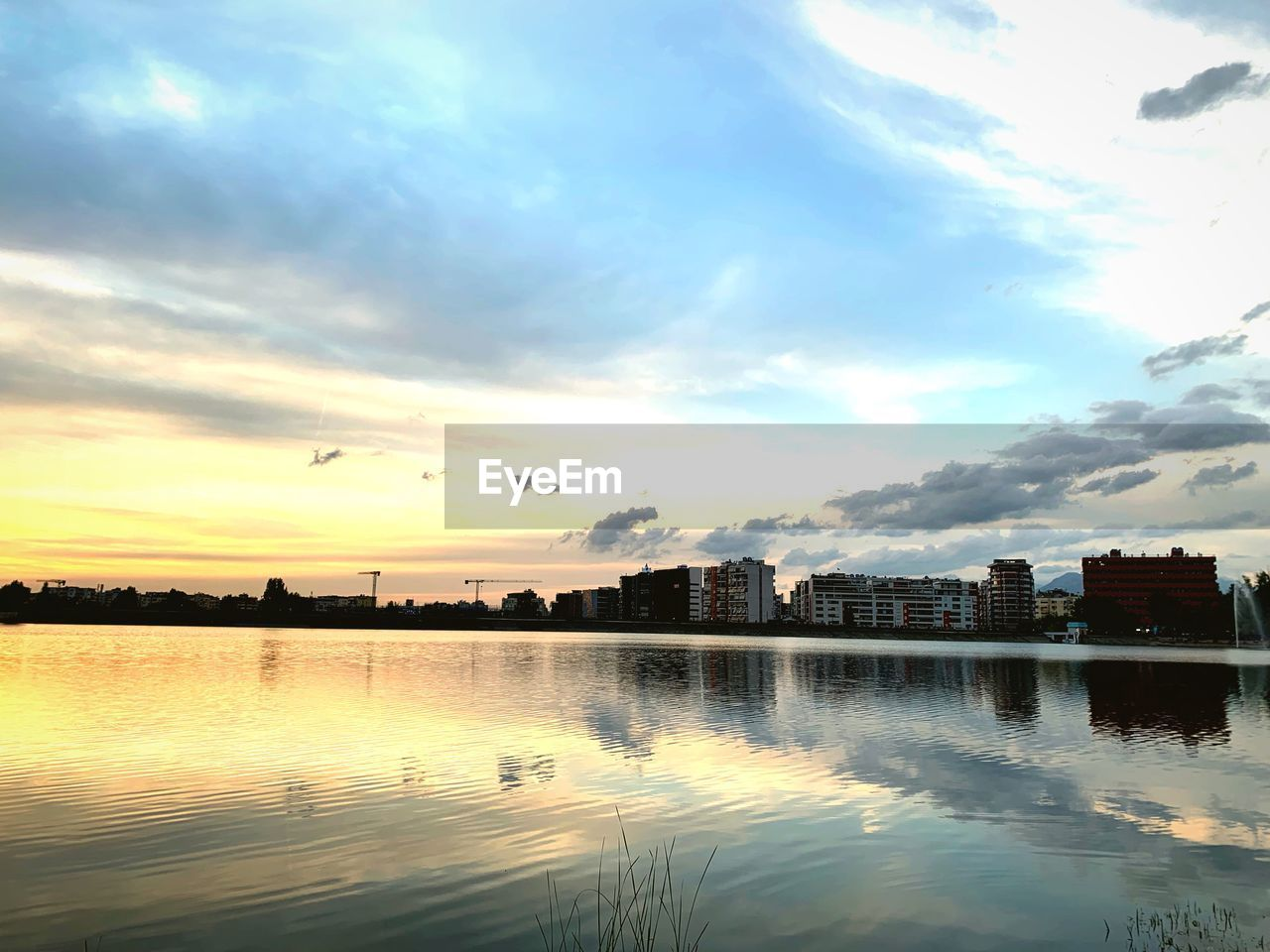sky, cloud - sky, water, building exterior, architecture, reflection, built structure, sunset, nature, waterfront, building, no people, city, beauty in nature, scenics - nature, lake, outdoors, tranquility, silhouette, cityscape