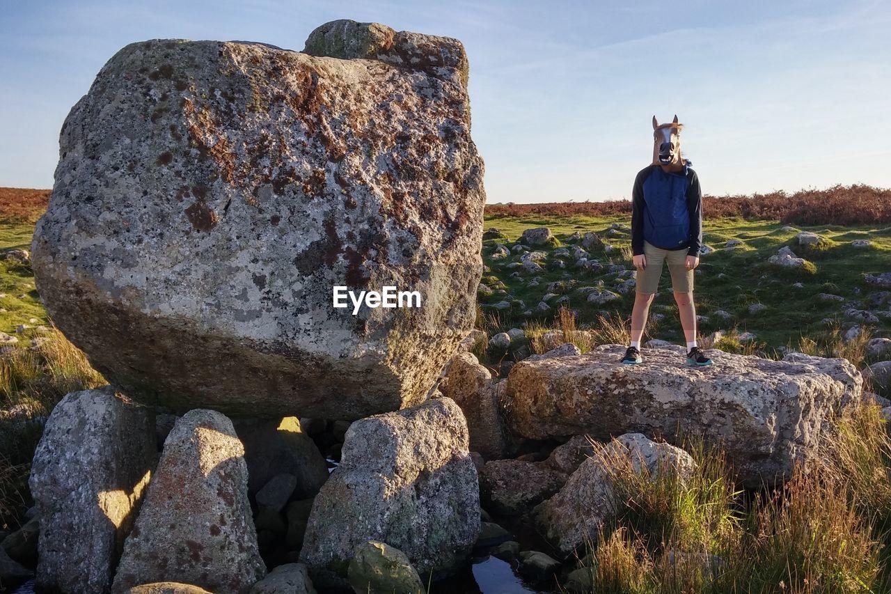 Man Wearing Mask Standing On Rock