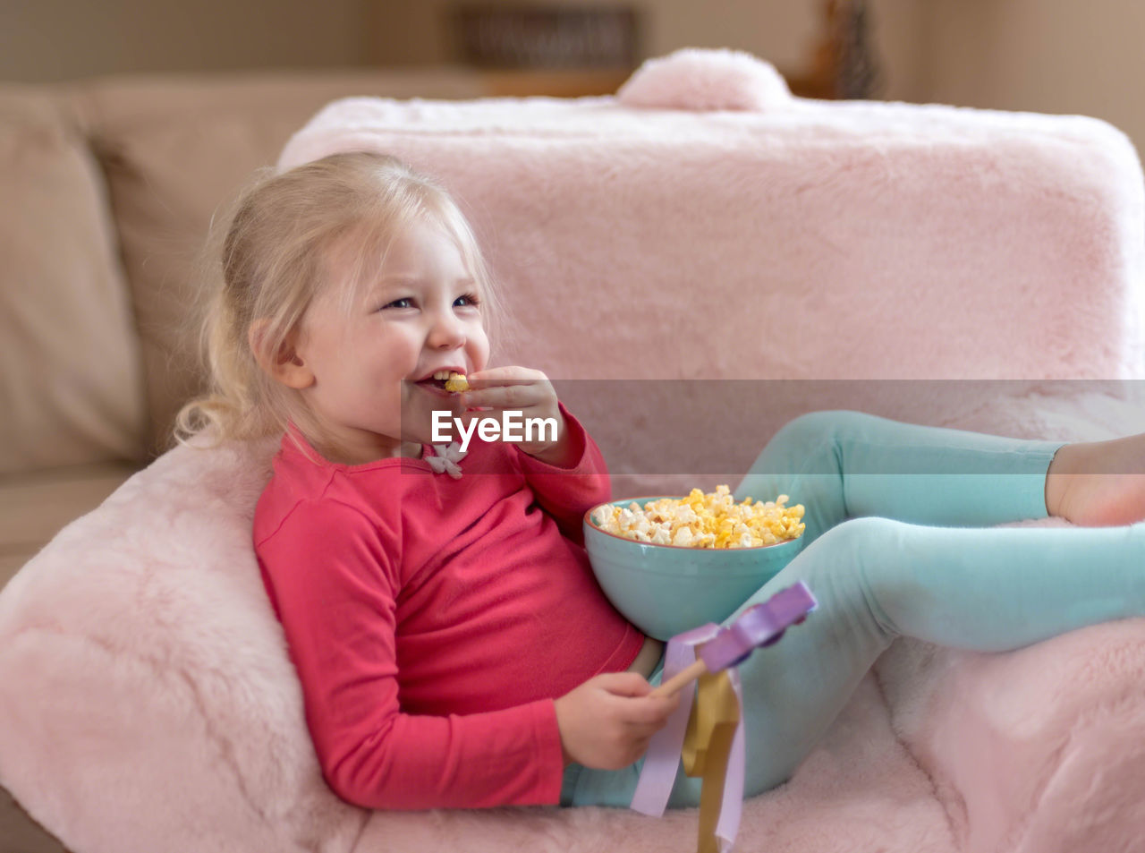 Cheerful Girl Eating Popcorns From Bowl While Relaxing On Chair At Home